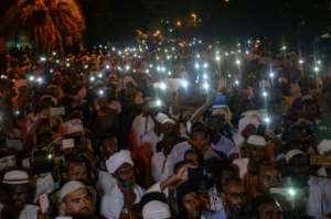 Supporters of Sudanese Islamist movements hold their phones up in the air as they chant slogans during a rally in front of the presidential palace on Saturday.  By MOHAMED EL-SHAHED (AFP)