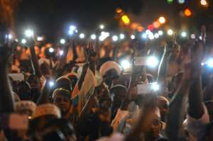 Supporters of Sudanese Islamist movements hold up their phones as they chant slogans during a rally in front of the presidential palace in downtown Khartoum. By MOHAMED EL-SHAHED (AFP)