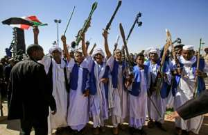 Supporters of Sudan's President Omar al-Bashir raise up sticks and swords in salute as they gather during a rally for him in the Green Square in the capital Khartoum on January 9, 2019.  By ASHRAF SHAZLY (AFP/File)