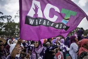 Supporters of the Tanzanian opposition political party The Alliance for Change and Transparency wave flags during a last campaign rally.  By MARCO LONGARI (AFP/File)