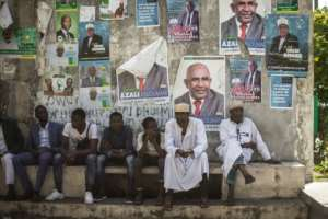 Supporters of the opposition Juwa Party sit beneath campaign posters, waiting for a rally in a village near Moroni. By GIANLUIGI GUERCIA (AFP)