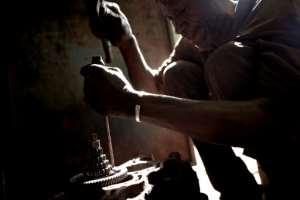 Surgery: A Bamako mechanic takes apart an old Vespa engine.  By MICHELE CATTANI (AFP)