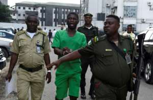 Suspected serial killer Gracious David-West, centre, being led into court on November 18.  By PIUS UTOMI EKPEI (AFP)