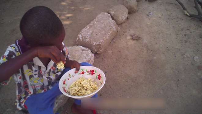 BOY EATING UNCOOKED INDOMIE FOR LUNCH