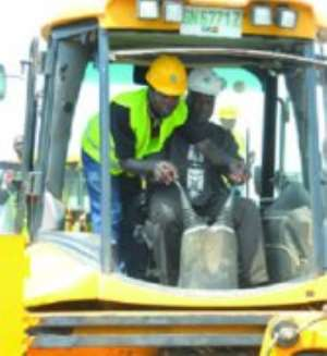 Vice-President  John  Mahama  using  an  excavator  to  cut  the  sod  for  commencement of work on the BRT project on the Graphic Road in Accra.