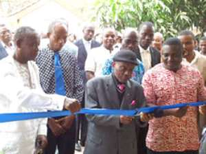 Mr. Godfred Medicene supporting Rev Mensah to cut the tape to inaugurate the new office complex