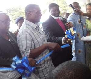 : President Mills cutting tape to officially open the NHIA building