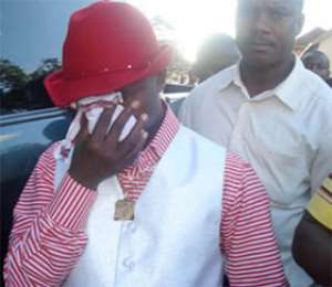 Rev Ebenezer wiping away tears at the prisons