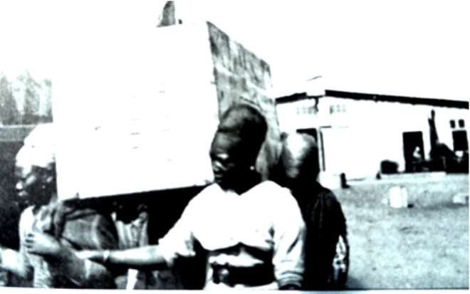 Herero women prisoners carrying heavy load.