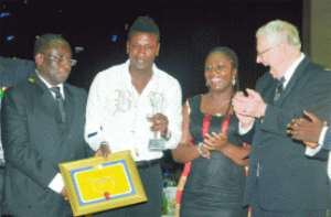 Asamoah Gyan (with trophy) being congratulated by the SWAG President, Ackah Anthony (left), SWAG Patron, Eposito (2nd right) after being crowned Sports Personality of the Year.