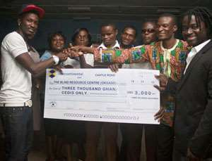Tinny presenting cheque to Mr Koufie, head of the resource centre (2nd right).