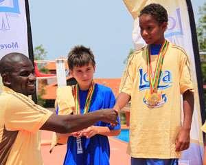 Promasidor's Inusah Musah (L) congratulating Tazana Kamanga Dybak of Lincoln Community School for winning the boys 100m breaststroke