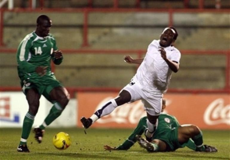 Ghana's Michael Essien, center, is brought down by Nigeria's George Abbey during their International friendly soccer match at Griffin Park Stadium, London, Tuesday Feb. 6, 2007. (AP Photo/Graham Hughes )