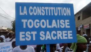 A demonstrator in Lome last week holds a banner reading