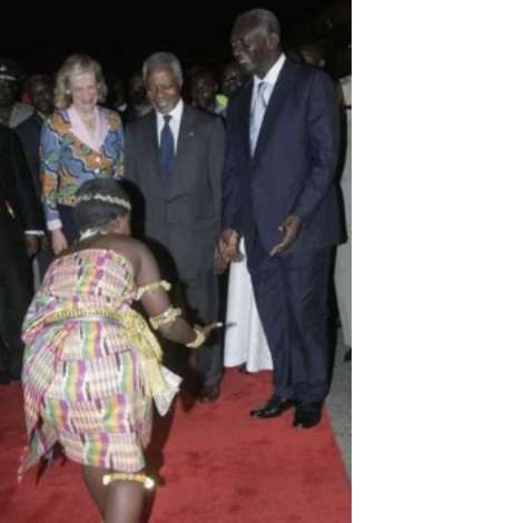 A traditional dancer entertains former U.N. Secretary-General Kofi Annan (C) and his wife Nane Annan upon their arrival at the Kotoka International Airport in Ghana's capital Accra January 23, 2007. Hundreds of cheering well-wishers, dancing and waving Ghanaian flags, greeted Annan when he arrived in his native Ghana after 10 years at the helm of the world body. Looking on is Ghana's President John Kufuor (R). Picture taken January 23, 2007. REUTERS/Yaw Bibini (GHANA)