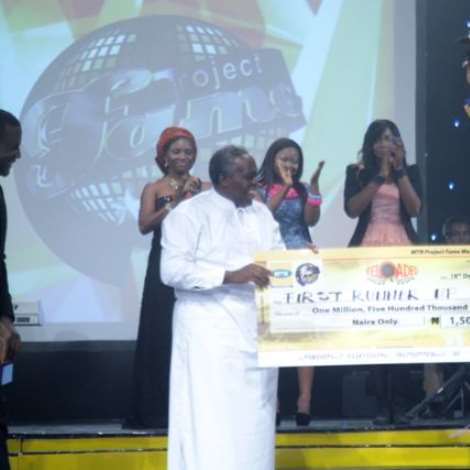 Olu Jacobs presenting Roy (1st Runner up) with his prize money and car keys