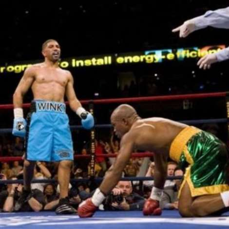 Ronald Wright (L) looks over to Ghana's Ike Quartey (R) after knocking him down in the second round of their middleweight boxing match in Tampa, Florida December 2, 2006.