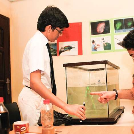 A STUDENT OF DPSI DEMONSTRATING HIS PROJECT ON TOTAL INTERNAL REFLECTION AS PARENT AND HIS SON OBSERVES