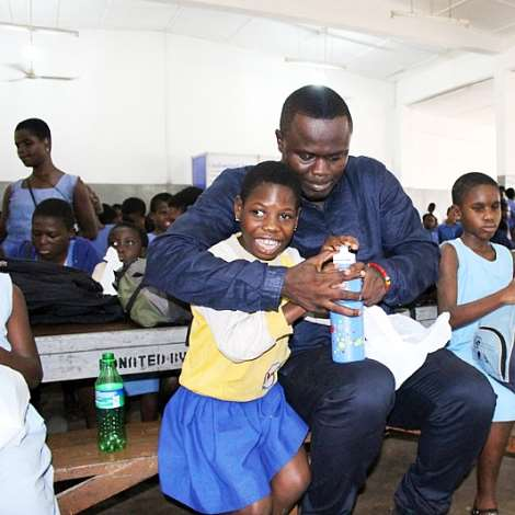 QWECI OTENG FEEDING A PUPIL OF THE AKROPONG SCHOOL FOR THE BLIND