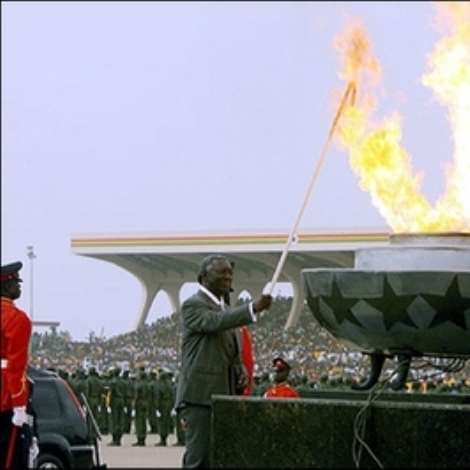 Ghana's president John Kufuor lights a flame symbolizing the spirit of independence at a ceremony in the packed Independence Square in Accra. Ghanaians turned out in their thousands Tuesday for colourful ceremonies marking independence from Britain 50 years ago when the country became the first black African state to break the bonds of colonial rule.(AFP/Kambou Sia)
