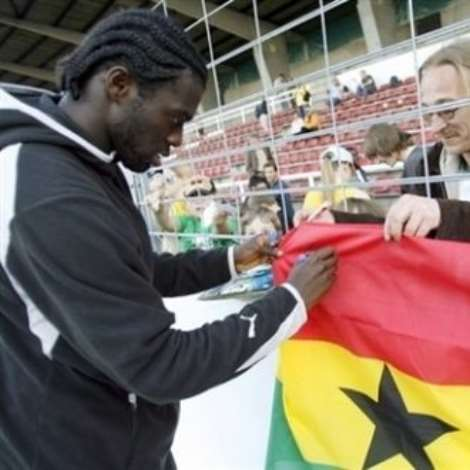 Wurzburg loves Ghana Defender Hans Sarpei autographs a Ghana flag for a fan during training at the Kickers Stadium in Wurzburg