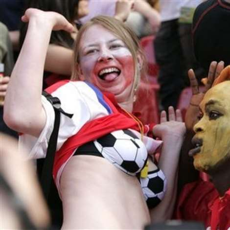 A supporter of he Czech Republic's team, left, sports a bra decorated with a soccer pattern as she jokes with a Ghana's supporter, prior to the World