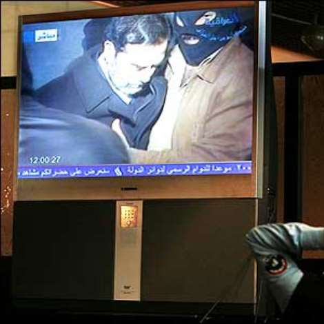 An Iraqi policeman watches TV coverage of the execution of the former Iraqi leader Saddam Hussein for crimes against humanity.