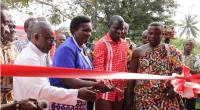 Mrs. Macaiver Ivy Quaye, District Director of Education (2nd from left) being assisted by Samuel Gyimah (2nd from right), National Distribution Manager-Airtel Ghana and Nana Krampah Kwame Saisi VIII to cut the tape to officially commission