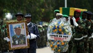Police officers and members of the Togolese army carry the casket and a picture of Sgt Landja Mozoboyo, one of the five Togolese peacekeepers killed in Mali, during a commemoration ceremony in Lome on July 8, 2016.  By Emile Kouton (AFP)