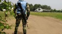 A UN peacekeeper in Abidjan, Ivory Coast stands guard by a UN helicopter used to transport officials and journalists on January 3, 2011.  By Issuof Sanogo (AFP/File)