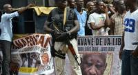 An armed man stands next to a banner featuring former Ivory Coast President Laurent Gbagbo during a meeting of the National Coalition for Change (CNC) party, on October 7, 2015 in Yopougon.  By Issouf Sanogo (AFP)