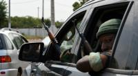 Ivory Coast soldiers sit in a car as they look outside the window with their rifles at the airport in Bouake on January 13, 2017.  By SIA KAMBOU (AFP)