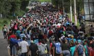 Some 1,500 Honduran immigrants walk north in a migrant caravan on Tuesday near Esquipulas, Guatemala. The caravan, the second of its size in 2018