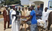 Chief Sissy left,presenting the items to Shafiu Mohammed, Al-Musahidin group leader.