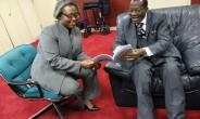 Daasebre Oti Boateng explaining a point in the book to Ambassador Pobee (Left)