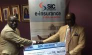 Andoh (L) receiving the dummy cheque from Adu-Poku