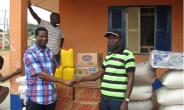 Mr. Obed Komla Adore of GCNAO in a hand-shake with Mr. Peter Uka Beidu (in cap)- manager of Adullam Orphanage in front of some of the donated items.