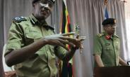 Taken on March 15, this photo shows Ugandan police spokesman Andrew Kaweesi (L) speaking to reporters in Kampala. On Friday, he was shot and killed as he left his home in Kampala.  By GAEL GRILHOT (AFP/File)
