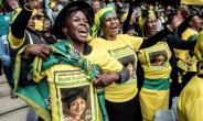 The ruling ANC's signature green, yellow and black adorned mourners' shirts and flags and women's head-wraps.  By MARCO LONGARI (AFP)