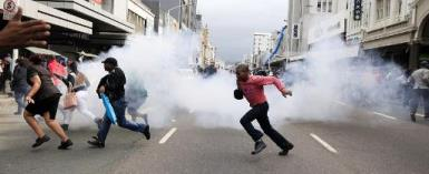 People run for cover from a stun grenade and tear gas after a skirmish between locals and foreign nationals as thousands of people take part in the