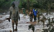 Villagers cross through receding waters in an area of flash flooding at Solai in Kenya's  Nakuru County after a private dam used for irrigation and fish farming burst its banks leaving at least 44 people dead..  By TONY KARUMBA (AFP)