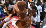 Visitors gather around a chocolate fountain at the opening of the fourth national cocoa and chocolate days in Abidjan.  By Sia KAMBOU (AFP)
