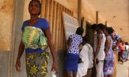 Voters consult an electoral notice in Lome's Be neighbourhood on polling day with 14 opposition groups urging a boycott citing