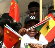 Young Senegalese wave flags to mark the arrival of President Xi on a state visit with China the west African nation's second biggest trading partner behind France, its firms having embarked on a slew of major infrastructure projects.  By SEYLLOU (AFP)