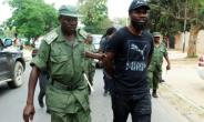 Zambian musician Chama Fumba, known as Pilato, is led away by police after the protest.  By DAWOOD SALIM (AFP)