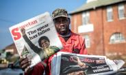 A newspaper seller holds up an edition featuring a story on the death of South African anti-apartheid campaigner Winnie Madikizela-Mandela, in Johannesburg on April 3, 2018.  By Gulshan KHAN (AFP)
