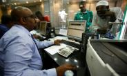 A dealer works at a foreign exchange office in central Khartoum on October 12, 2017, after the lifting of the US trade embargo came into effect, though the finance minister says banks around the world are still wary of working with the country.  By ASHRAF SHAZLY (AFP/File)