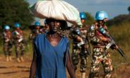 A displaced woman carries goods on her head as United Nations Mission in South Sudan (UNMISS) peacekeepers patrol outside the premises of the UN Protection of Civilians (PoC) site in Juba on October 4, 2016.  By Albert Gonzalez Farran (AFP)