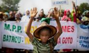 A Fulani boy marches in front of a sign that reads