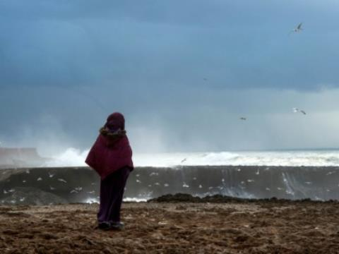 A file picture shows a Moroccan woman looking out to sea during a storm in Rabat on January 8, 2018.  By FADEL SENNA (AFP/File)